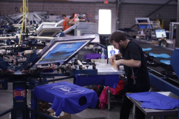 Homme-en-t-shirt-imprimant-boutique-utilisant-un-outil